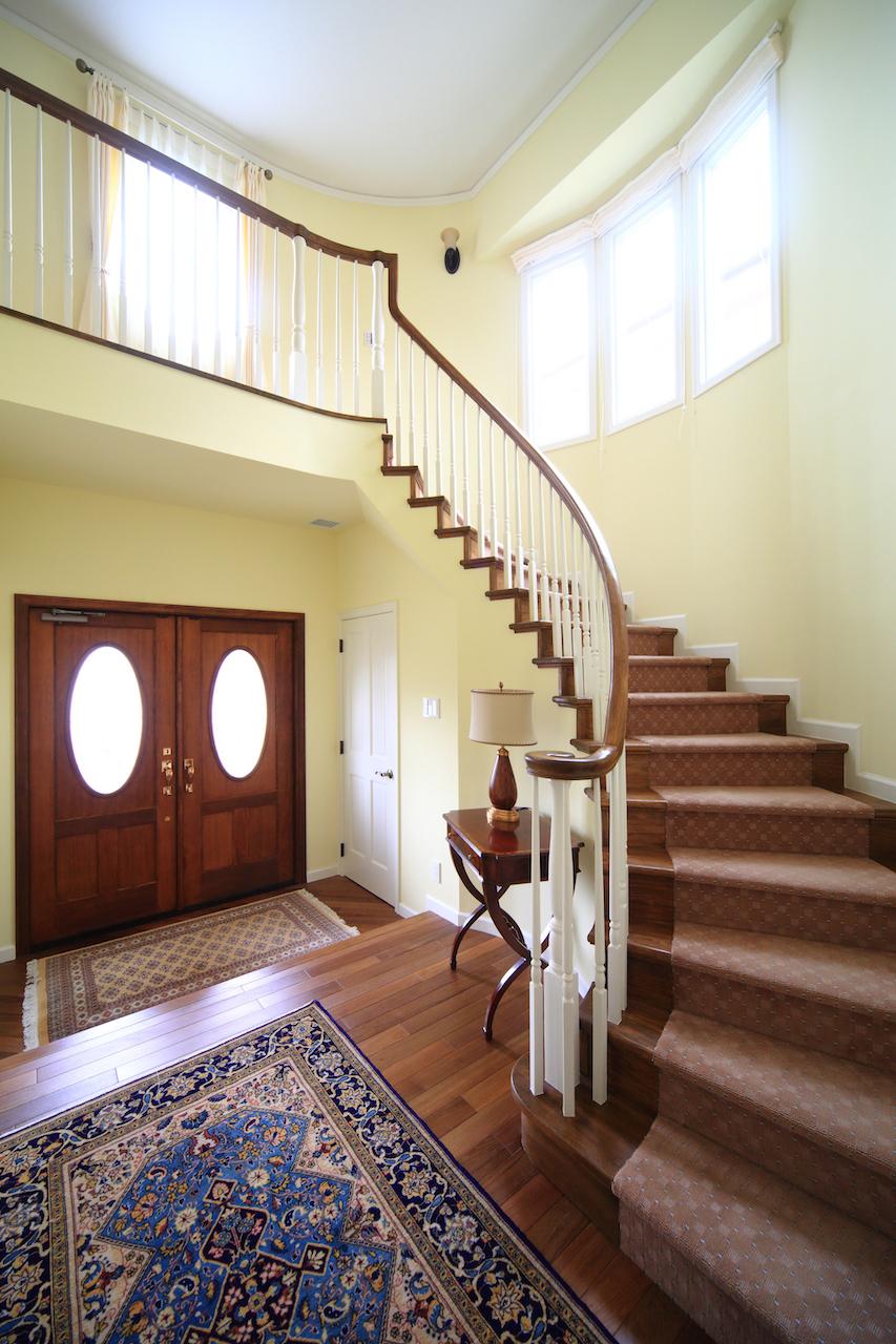 両開きの玄関ドア、吹抜けのホールにサーキュラー階段