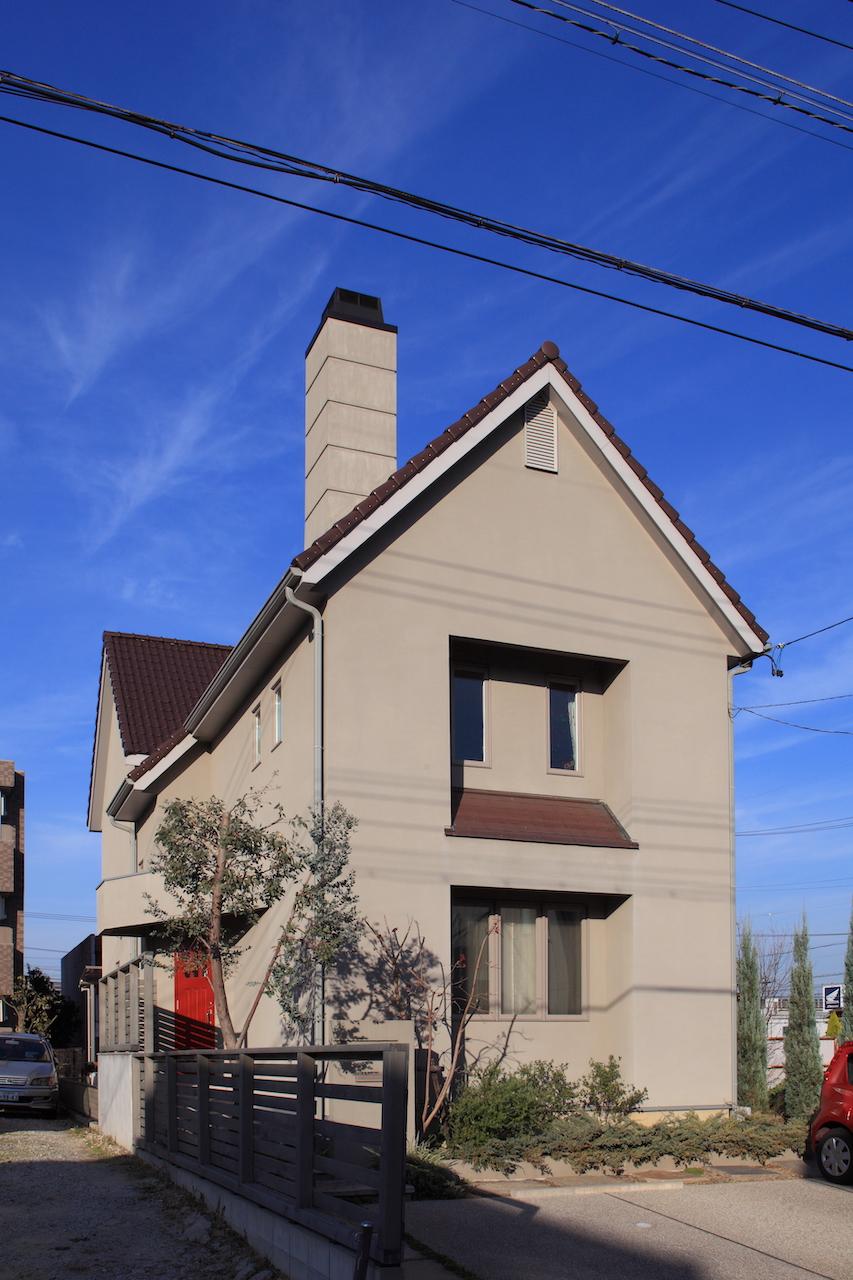 グレーの落ち着いた外観カラー、赤い玄関ドアと煙突が印象的。