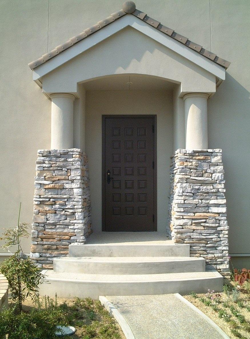 石積みの柱が印象的なファサード。木製の板チョコ玄関ドアー。