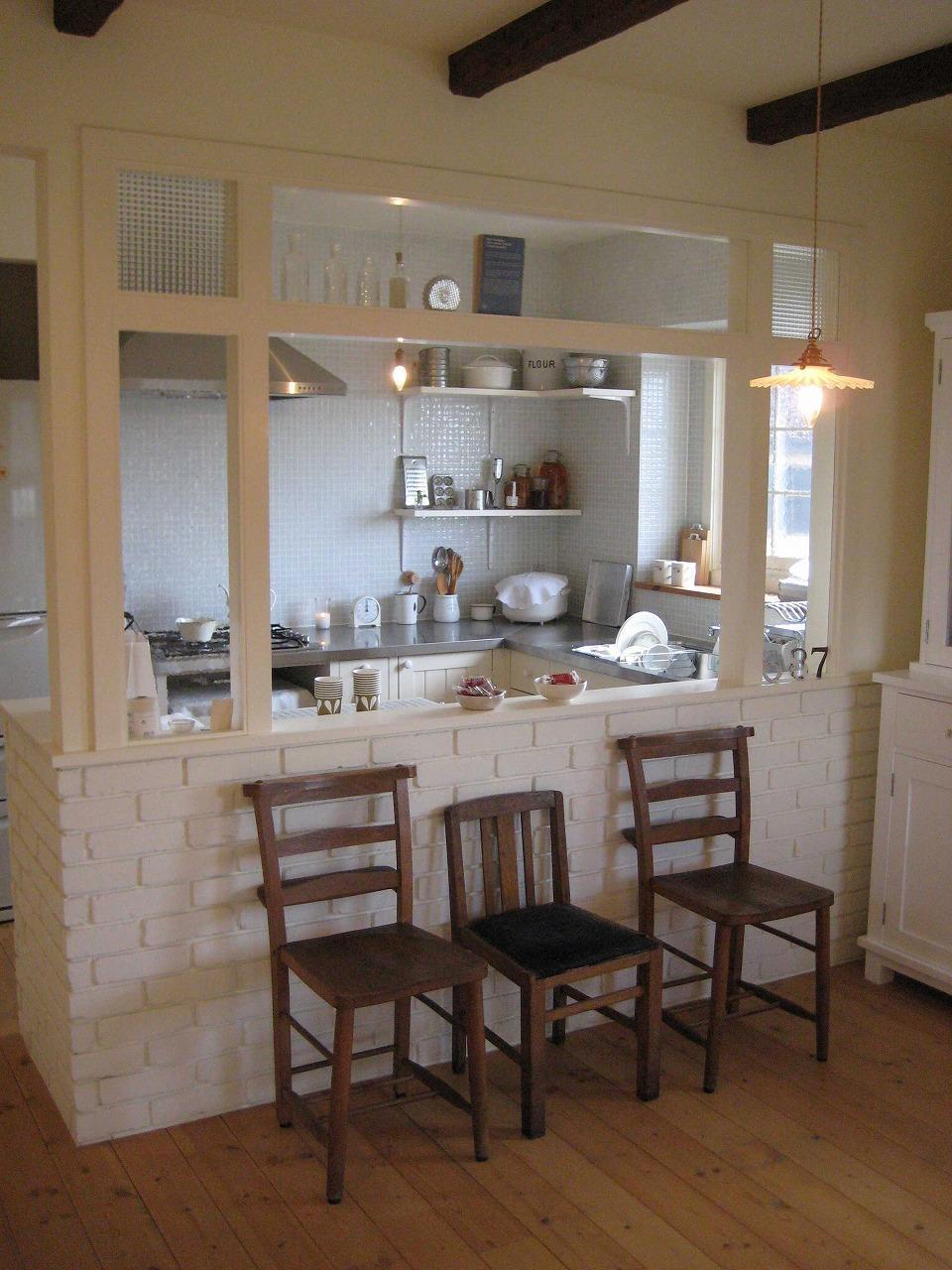 カフェのようなキッチン。ガラスパーテーションに、木枠やレンガはすべて白く塗装。