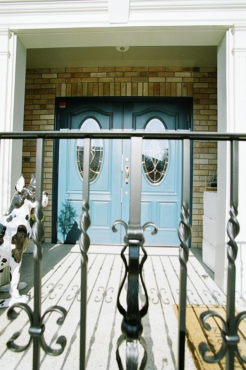 両開き玄関ドア、レンガ貼りの重厚感あるエントランス
