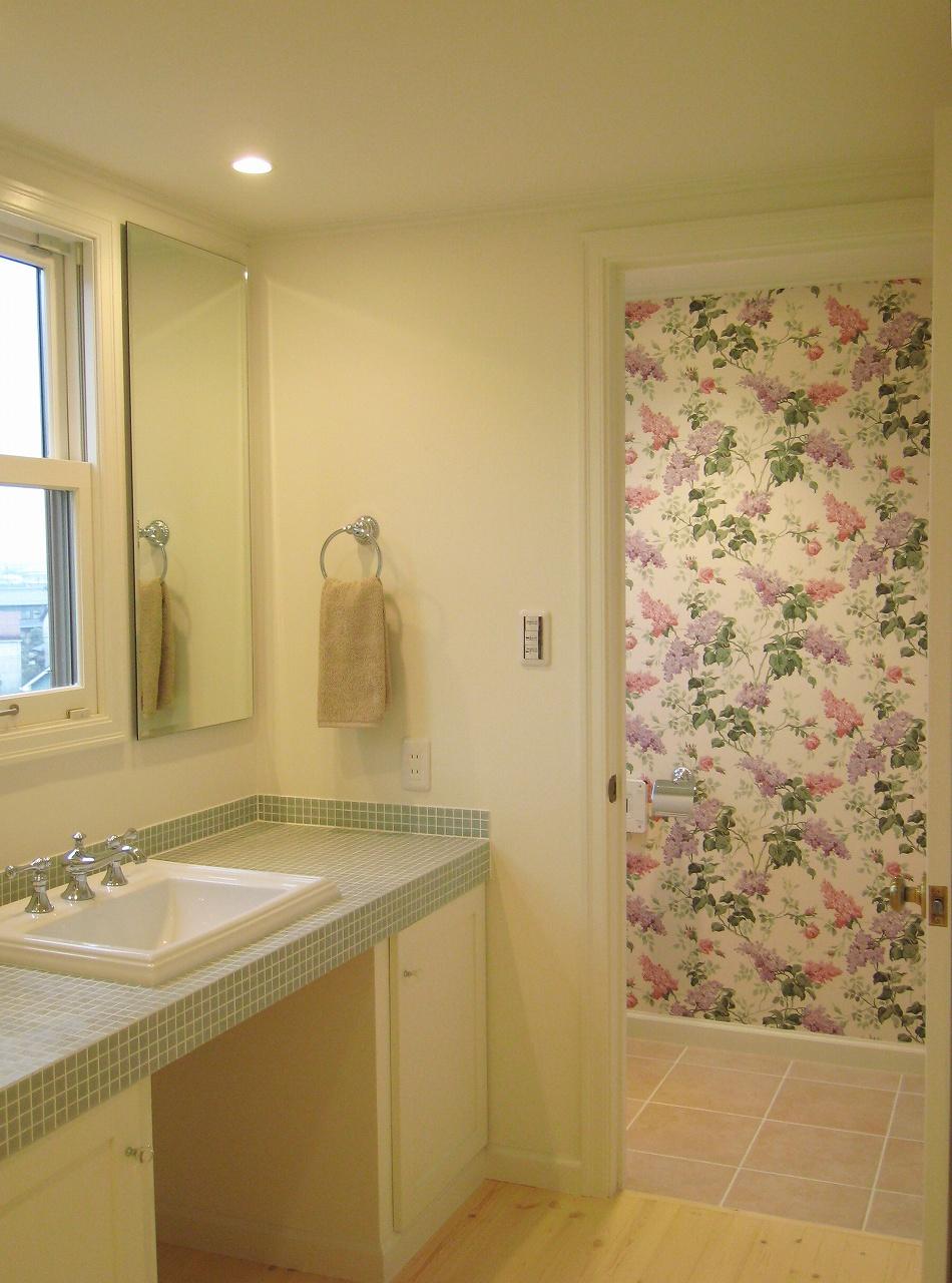 タイル貼りの洗面台、奥のトイレは花柄の輸入クロス(アクセントクロス)で華やかに。