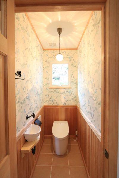 クロスと板張り(腰板)で表情豊かにした、トイレ。ペーパーホルダーなどのアクセサリーはアイアンで統一。