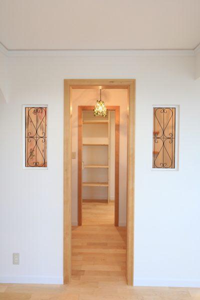 家事室とパントリーへ続く、かわいい木製開口とニッチ装飾