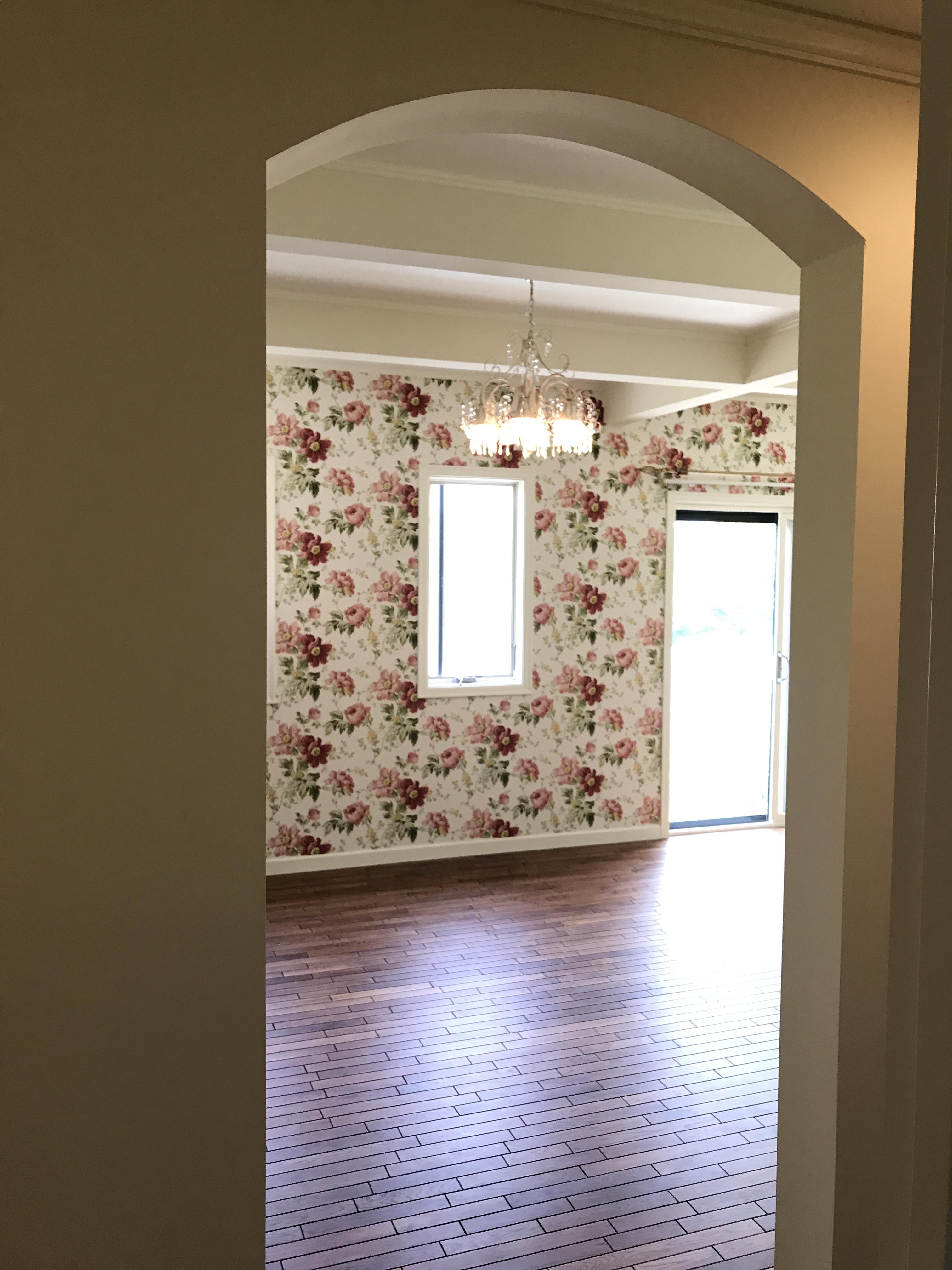 ダイニングルームの開口はアーチトップに、一面のアクセントクロスは花柄でエレガントに