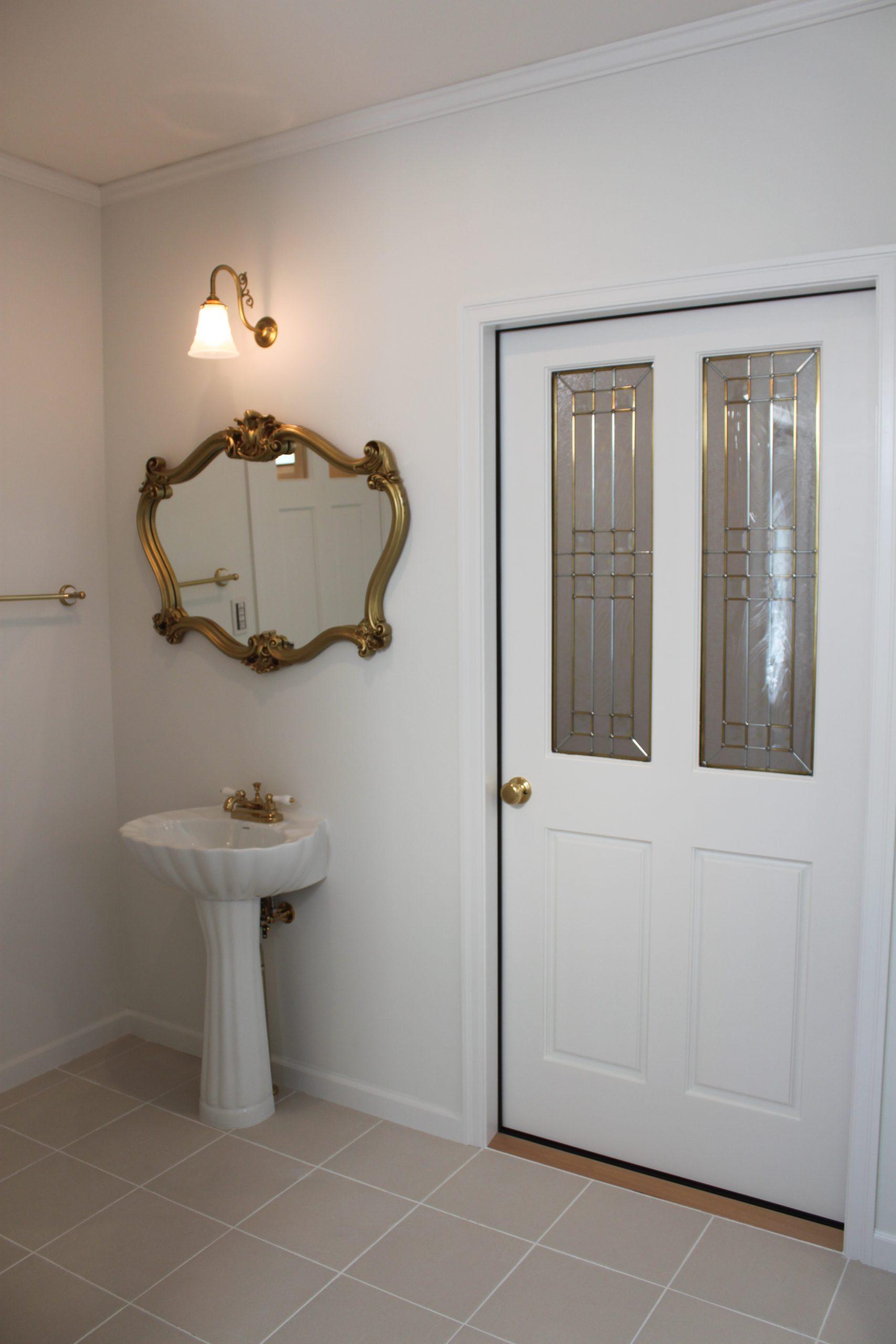 ペデスタル手洗い、ゴールドのミラー。扉もステンドガラス入り。
