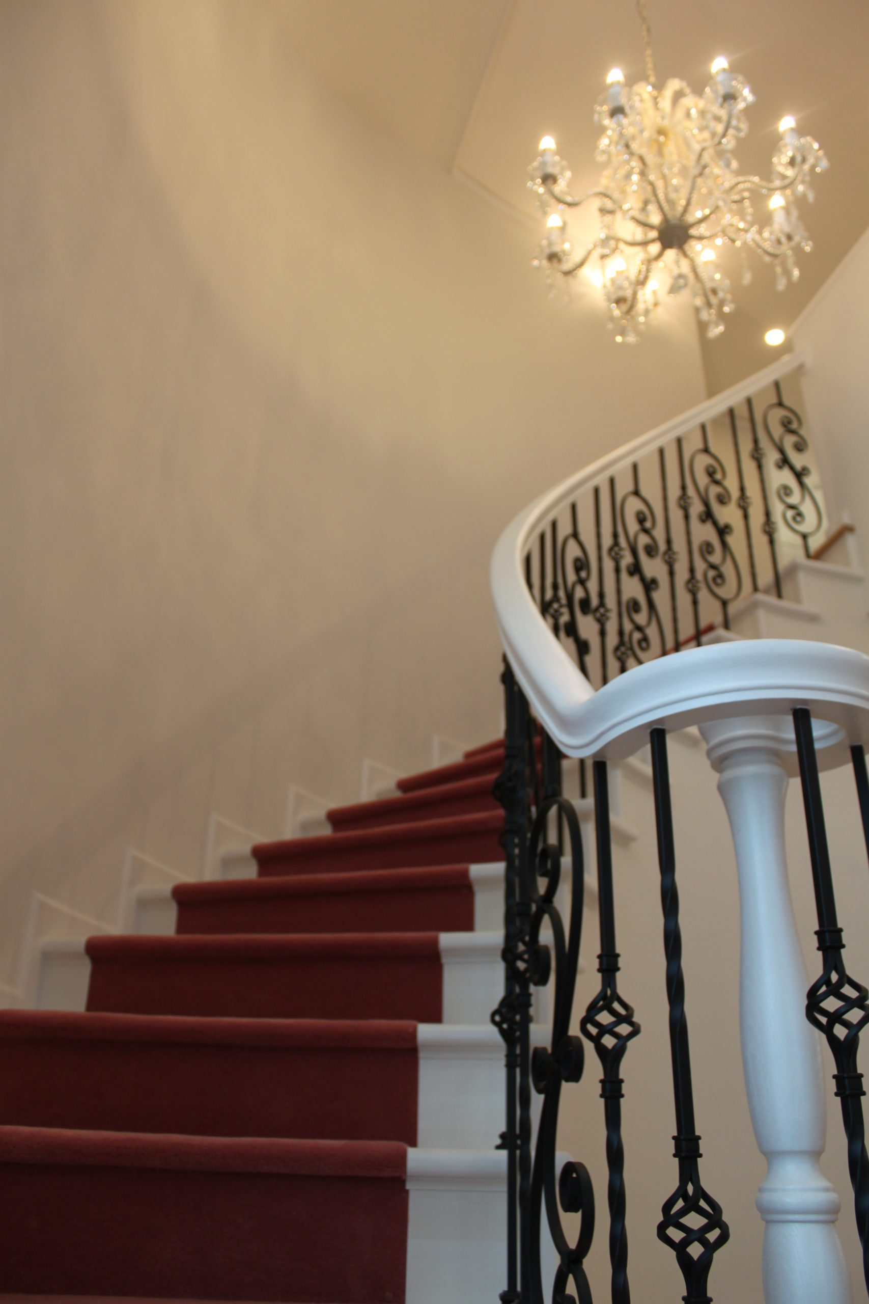 階段はピンク色のカーペット敷きに。階段と手摺レールをエレガントな白色に塗装。