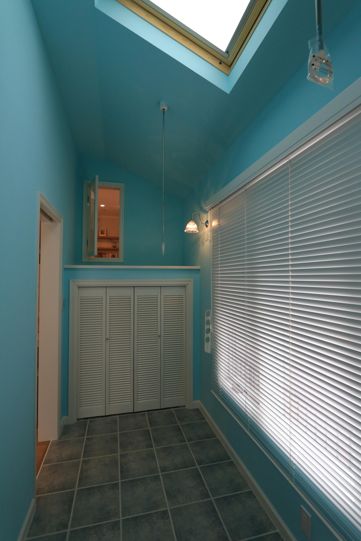 吹抜け斜め天井の広い洗濯室、爽やかな青色のランドリールーム。