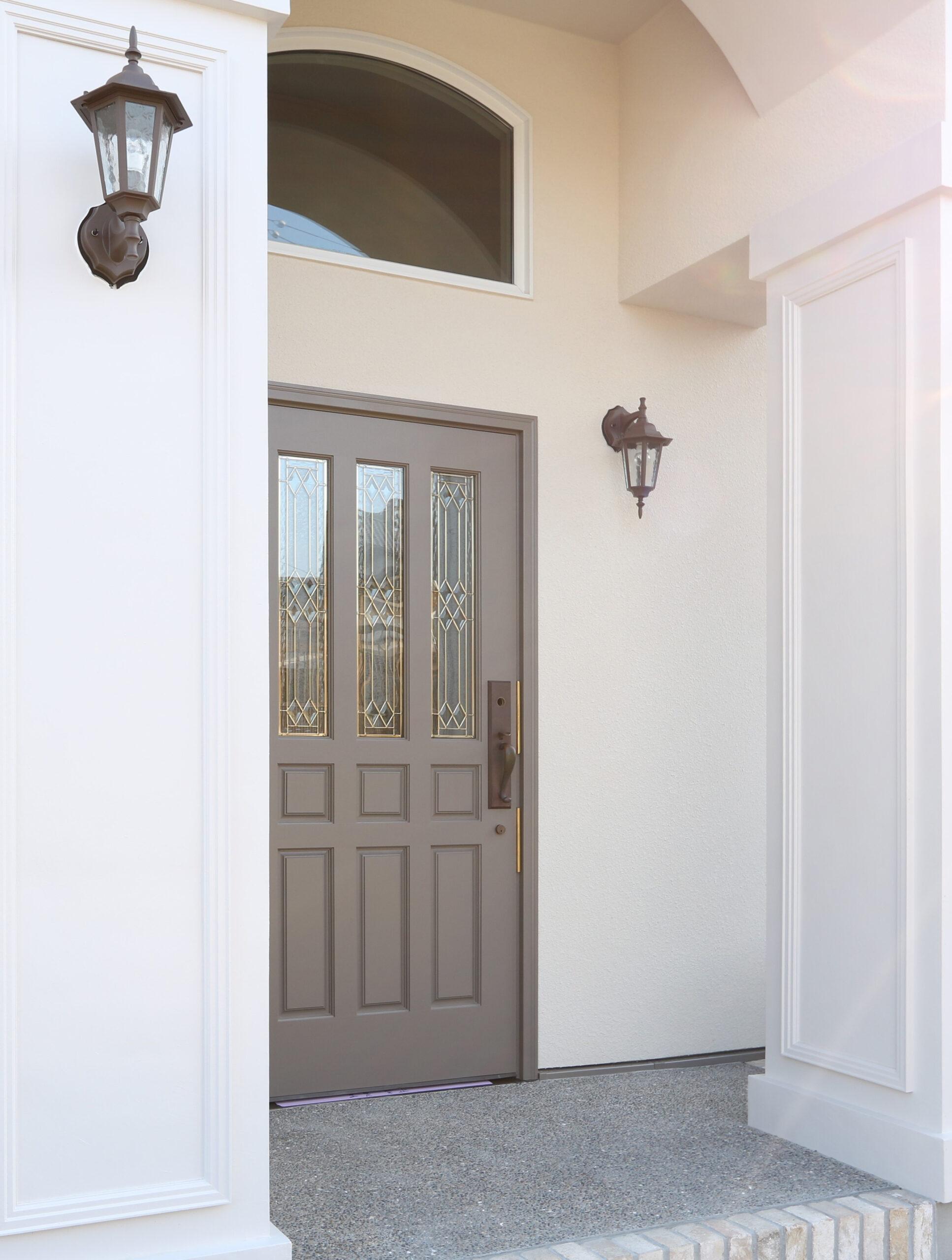 木製ドアをグレージュに塗装。照明器具もシャビーシックなセレクト。アーチ吹抜けのデザイン柱が奥行感を増します。