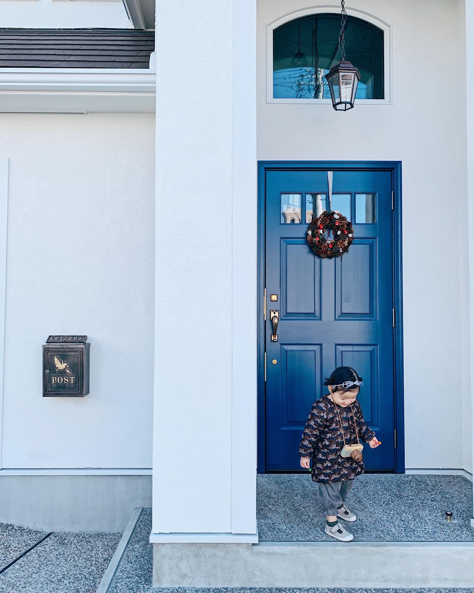 青色のがポイントの家。重厚な木製玄関ドアがアメリカ製。