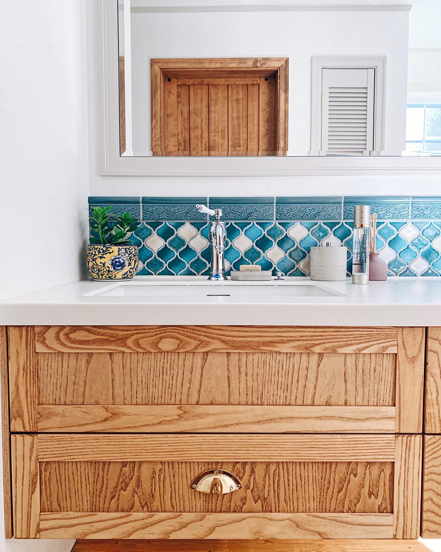 カスタムオーダーの洗面所には、コラベルタイルを貼ってレトロ感をプラス。